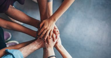 Paralysis Resource Center aid for ALS | ALS News Today | people putting hands in supportive huddle