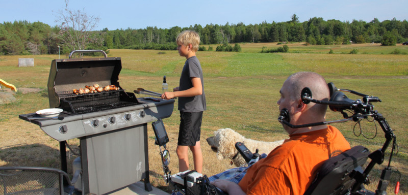 Cooking \ ALS News Today \ Kristin's son Isaac cooks chicken on the outdoor grill while his dad, Todd, coaches him.